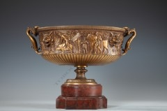 A fine Greek style two handled « jardinière » made of gilded and patinated bronze. The body decorated in frieze and low-relief with male and female figures walking in procession with offerings, with lion's heads coming in between.