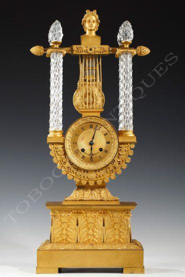 Pendule au buste d'Apollon en bronze doré et cristal - Tobogan Antiques - Antiquaire Paris